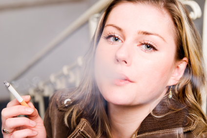 A woman smoking a cigarette and putting her self at risk for oral cancer.