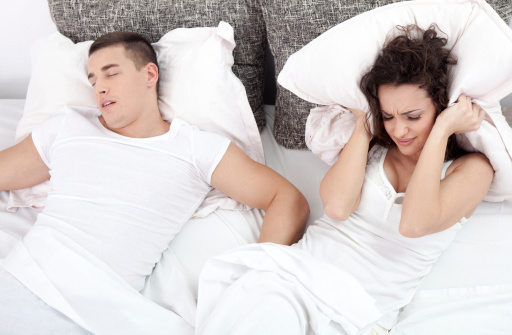 A man suffering from sleep apnea snoring loudly and keeping his wife awake!