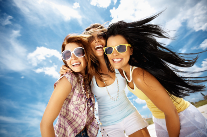 Three women wearing sunglasses and smiling after one of them got new teeth in an hour by her Glendale Oral Surgeon at Arrowhead Oral and Maxillofacial Surgery, after she lost her teeth in a car accident.